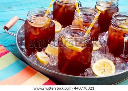 Mason jar mugs filled with iced tea and fresh lemon with yellow swirled straw on ice in round steel tub sitting on bright blue wooden table with striped multi-colored napkin