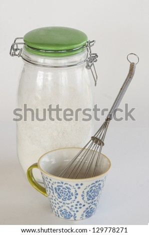 mason jar with flour and cup and whisk - stock photo
