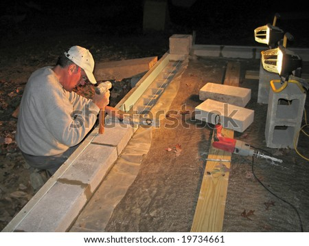 Mason laying block wall at night under lights - stock photo