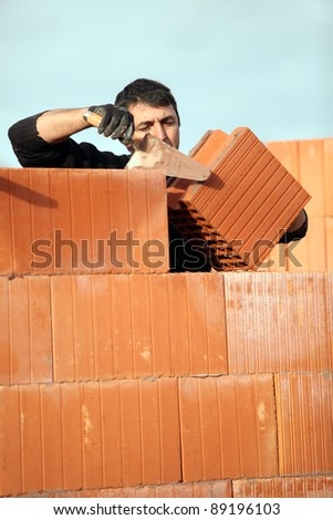 Mason laying bricks - stock photo