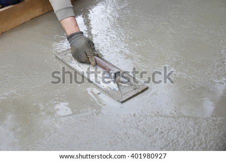 Mason leveling screeding concrete floor base stock photo 401980927 mason leveling and screeding concrete floor base with square trowel in front of the house solutioingenieria Images