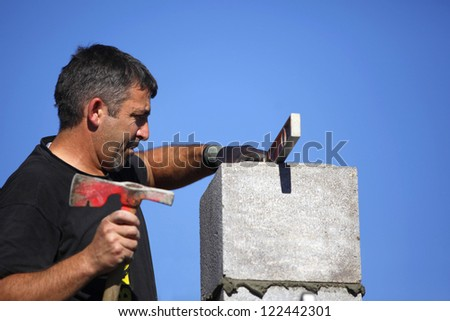 Mason making adjustment to wall - stock photo
