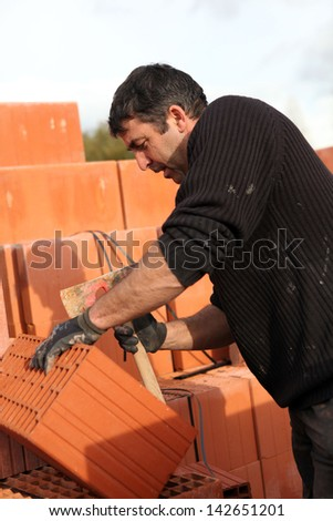 Mason making adjustments to brick - stock photo