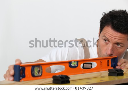 Mason measuring plank of wood - stock photo