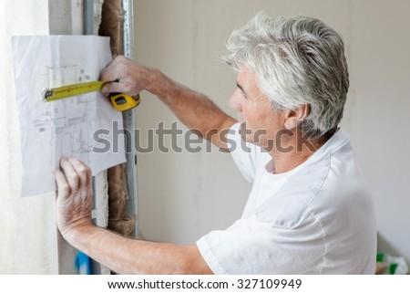 Mason measuring plans - stock photo