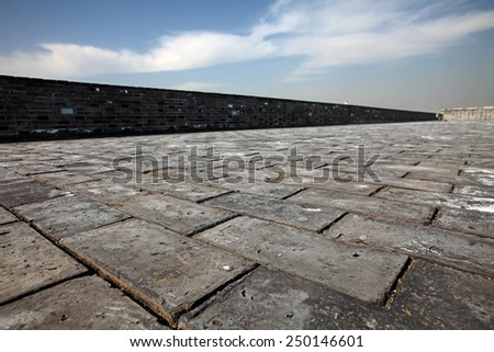 Mason pathway on top of an ancient castle wall against a blue cloudy sky.  - stock photo