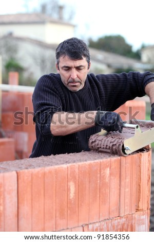 Mason pouring cement onto wall - stock photo