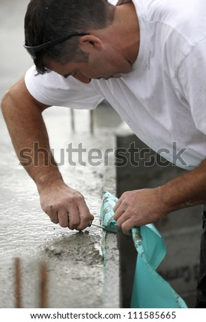 Mason removing plastic sheet from wall - stock photo