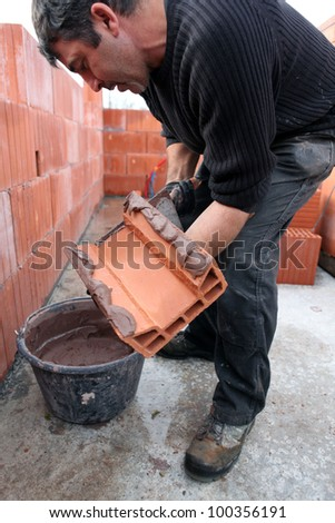 Mason spreading cement on brick - stock photo