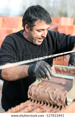 Mason using special device to pour cement on wall - stock photo