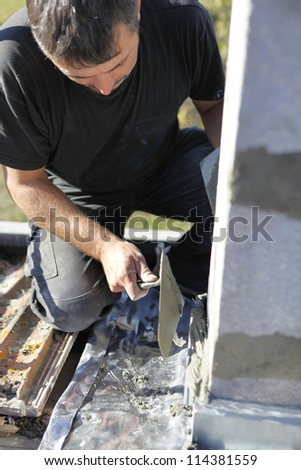 Mason using trowel to spread cement on wall - stock photo