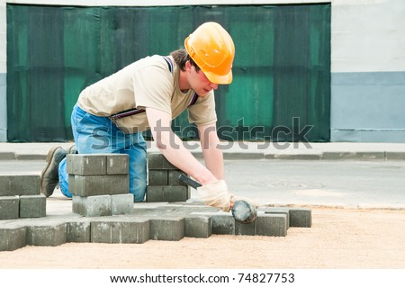 mason worker making sidewalk pavement with stone blocks - stock photo