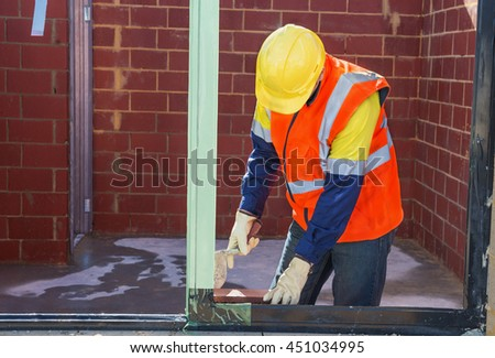 mason worker performing work on the construction site of house - stock photo