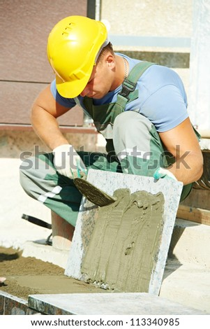 mason worker tiler making stairway from granite stone tile blocks - stock photo