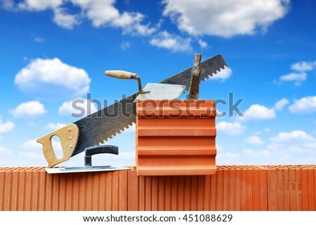 Masonry tools on a brick wall. Bricklaying work. - stock photo