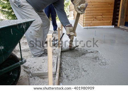Masons filling wood form with a shovel of concrete mix for floor base in front of the house. Construction business and tools, do-it-yourself, basic work around the house concept.  - stock photo