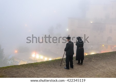MASOULEH, IRAN - OCTOBER 05, 2014: Elderly couple on the edge of the roof, view over mountain village Masouleh in a mist