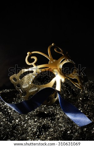 Masquerade carnival mask against a dark background. Concept image for traditional New Years Eve party with ribbon and accommodation for copy space. - stock photo