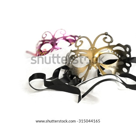 Masquerade carnival masks against a white background. Concept image for traditional New Years Eve party with ribbon and accommodation for copy space. - stock photo