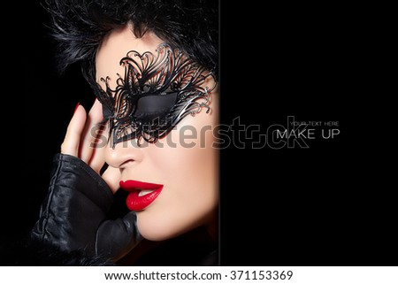 Masquerade. Short hair gorgeous woman wearing elegant black mask and trendy mittens. Sexy lips and nails. Beauty and makeup concept. High fashion portrait isolated on black background with sample text - stock photo