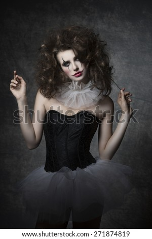 masquerade woman with vintage dancer dress, sad clown make-up and uncombed hair. Romantic fashion portrait  - stock photo