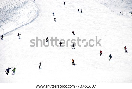 Mass descent of mountain skiers from a wide hillside - stock photo
