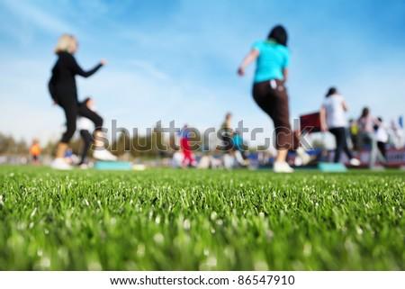 mass fitness at stadium at sunny autumn day, focus on green grass - stock photo