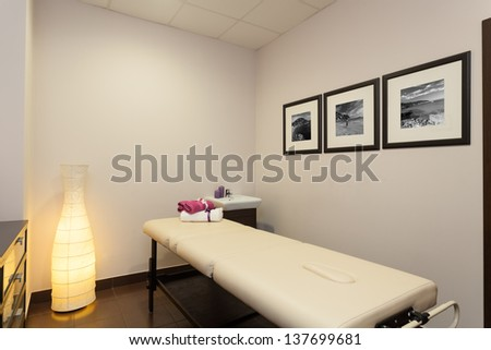 Massage bed and equipment in modern room - stock photo
