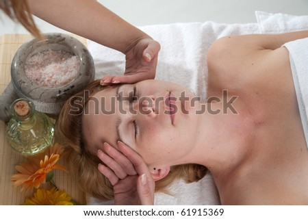 Massage - Cute young girl is having a massahe in a wellness centre - stock photo