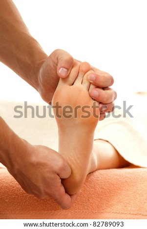 massage foot female close-up isolated on white background