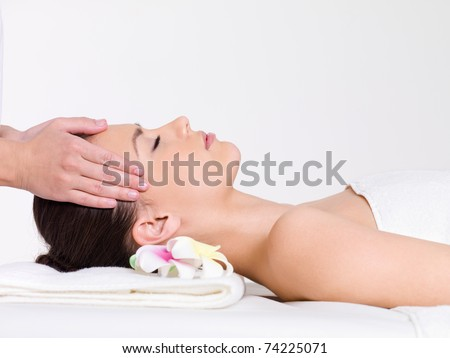 Massage for the face of young beautiful woman - horizontal - stock photo