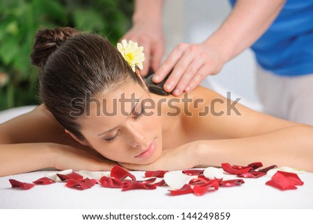 Massage Hot Mineral Stone Treatment at Day Spa by Masseuse - stock photo