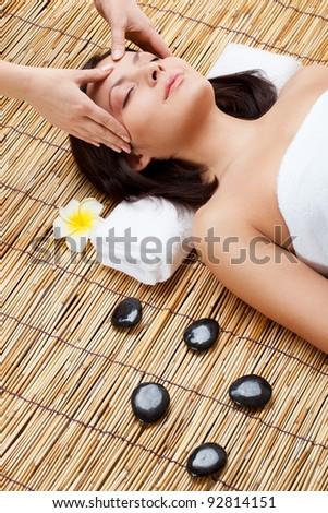 massage in spa salon, woman laying on bamboo mat - stock photo