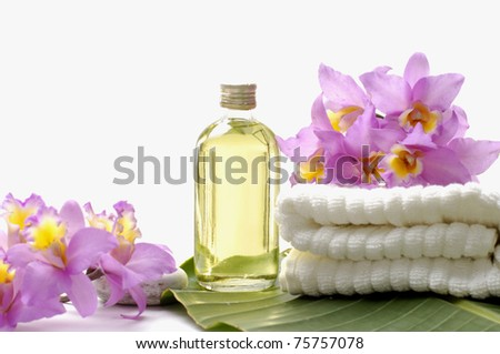 massage lotion and pink orchid on towel-spa essentials - stock photo