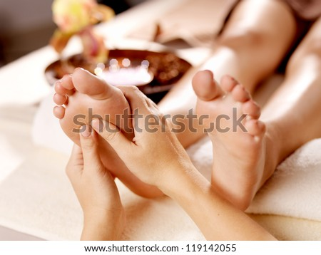 Massage of human foot in spa salon - Soft focus image - stock photo