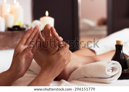 Massage of human foot in spa salon - Soft focus image - stock photo