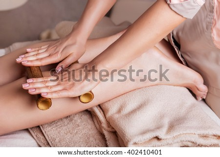 Massage of human foot in spa salon  with bamboo sticks. Closeup of feet, - stock photo