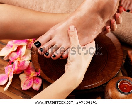 Massage of woman's foot in spa salon - Beauty treatment concept - stock photo