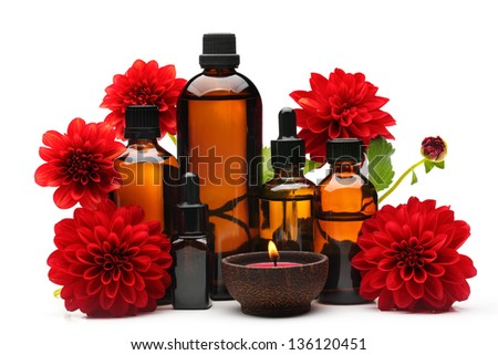 Massage oil,burning candle and red dahlia flower,isolated on white. - stock photo