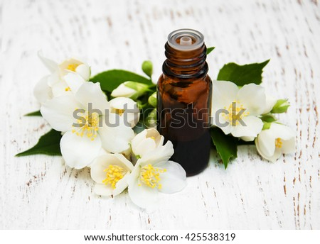 Massage oil with jasmine flowers on a wooden background