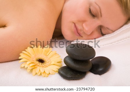 Massage session for a woman at the spa center with volcanic stones