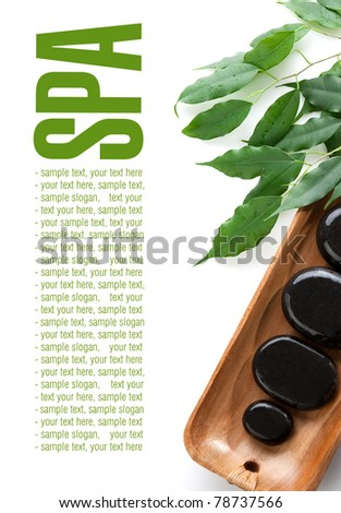 Massage Stones and green leaves on wooden tray. Space for text isolated on white. - stock photo