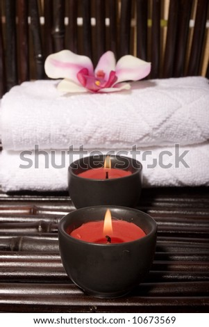 Massage stones and orchid flowers on bamboo - stock photo