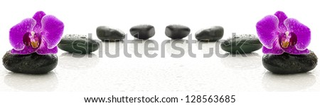 Massage stones and purple orchid with water drops representing a wellness concept. - stock photo
