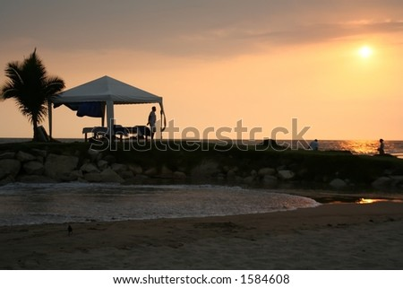 Massage table and tent on the beach at sunset. - stock photo