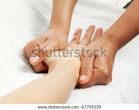 massage therapist gently kneading female hand - stock photo