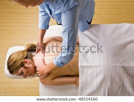 Massage therapist giving woman massage - stock photo