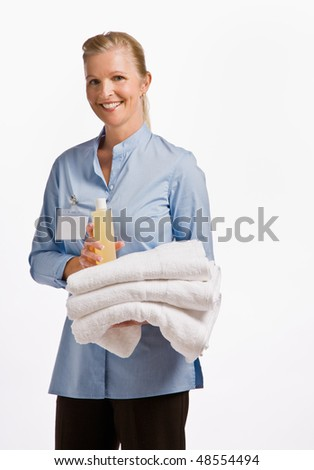 Massage therapist holding oil and towels - stock photo