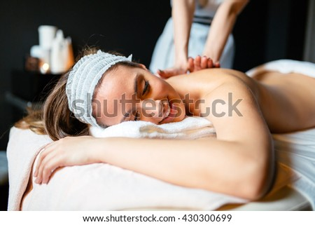 Massage therapist massaging beautiful brunette - stock photo
