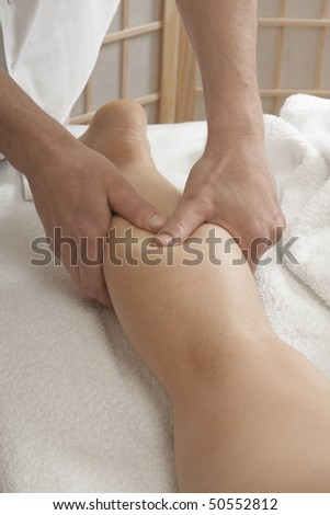 Massager's hands working with a woman's leg. Practice of reflexotherapy. - stock photo